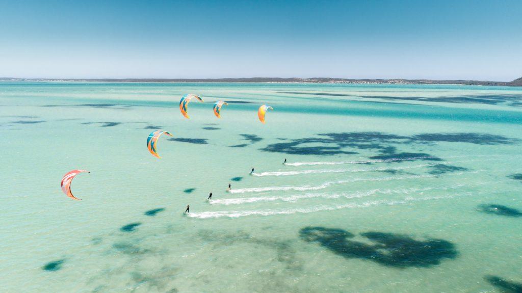 kitesurfers-en-ligne-dans-eau-turquoise