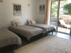 belle chambre lumineuse avec lits simples accès jardin