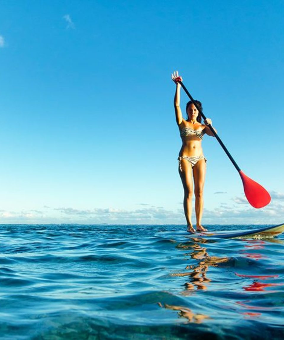 young woman stand up paddling in pristine lagoon