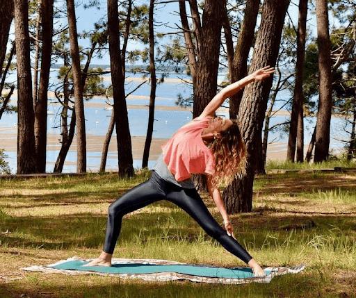 femme en posture de yoga dans la foret proche de la plage