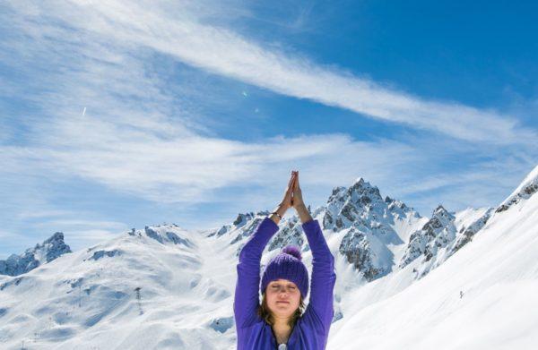Femme en plein stage yoga du froid en montagne