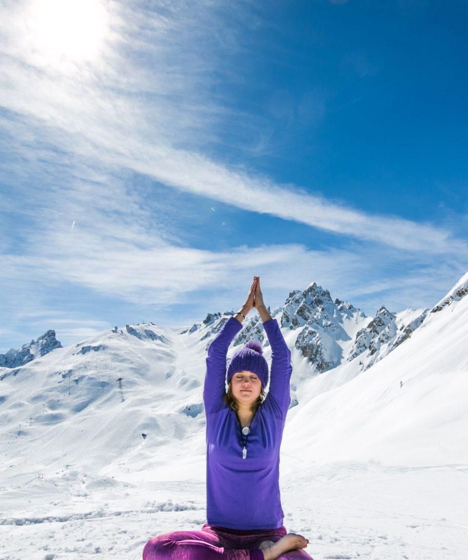 Femme assise qui fait du yoga dans la neige
