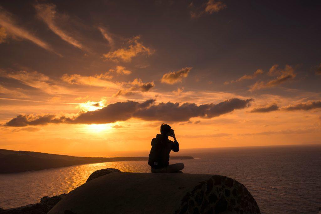 Un homme aimant voyager autour du monde admire le coucher du soleil propice à la méditation