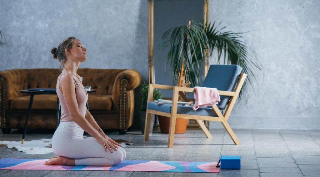 Femme méditant sur son tapis de yoga