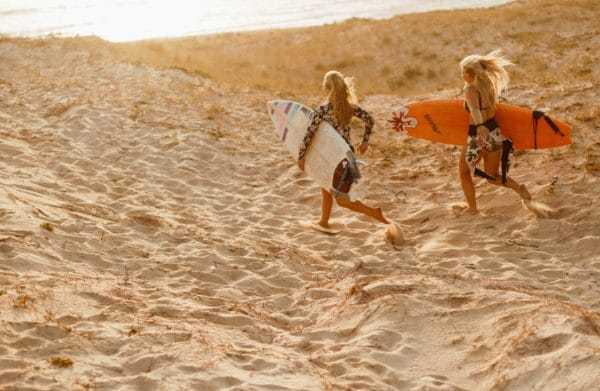 deux femmes passionnées de séjours sportifs prêtes à surfer sur la plage après un stage deméditation et de yoga